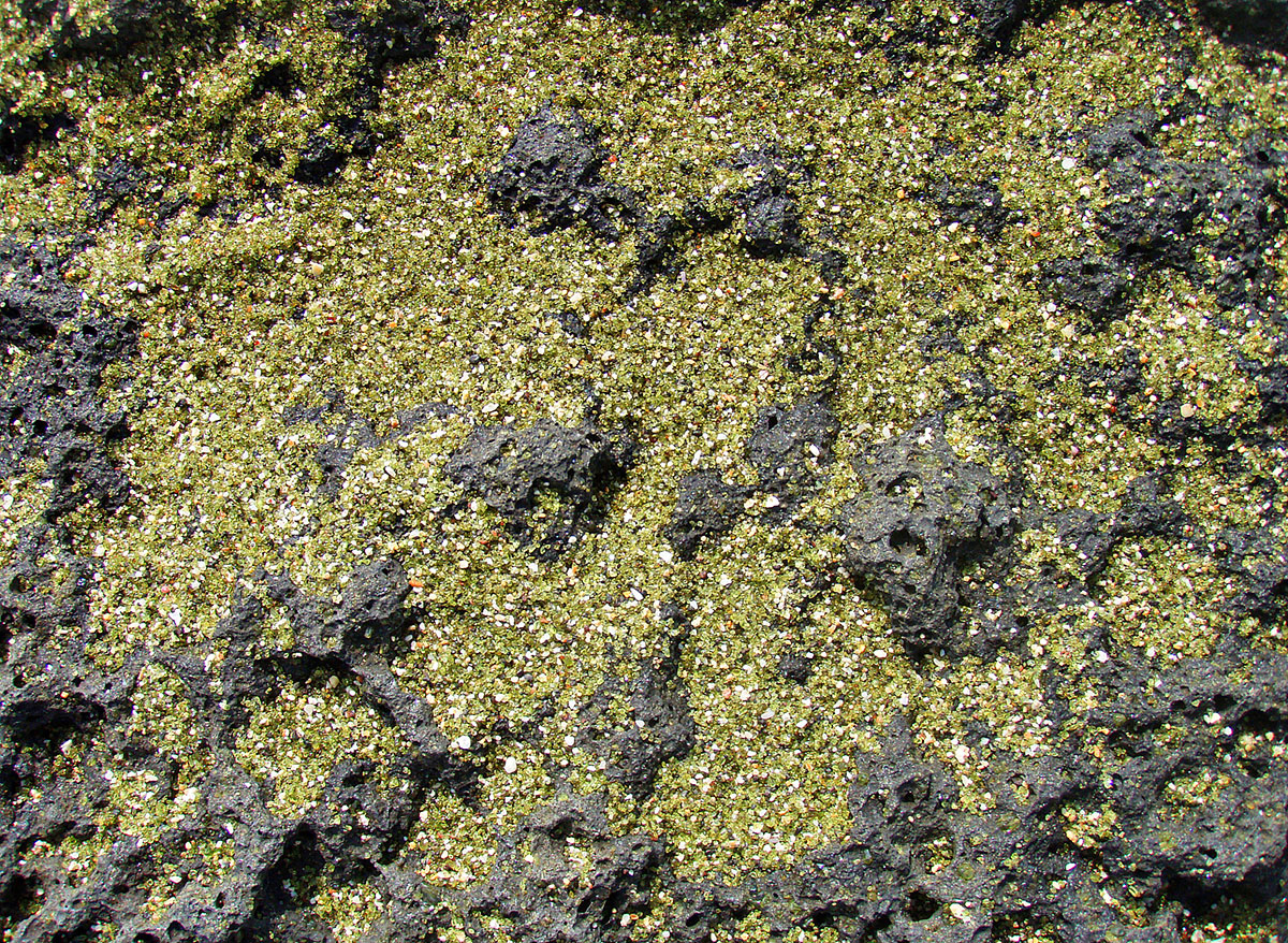 Green olivine sand on the lava beach