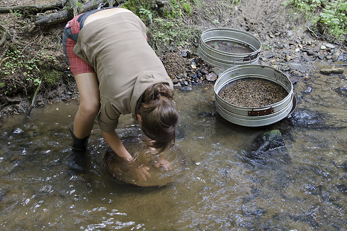 Young lady gold panning in the small creek
