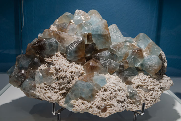 Cluster of bicolor topaz crystals on cleavelandite from Volodarsk, Ukraine