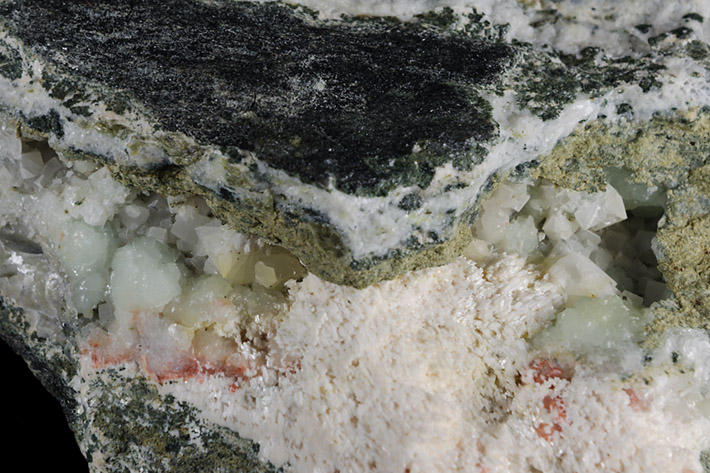 Detail of alpine vein with green prehnite, olive green clinozoisite, pink laumontite and white calcite from Markovice quarry in Czech Republic