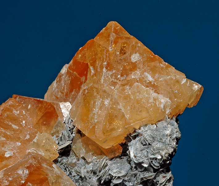 Tetragonal dipyramide shaped crystals of orange scheelite on muscovite mica from Yaogangxian Mine, Hunan Province, China